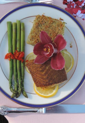 Salmon and asparagus on a china plate, garnished with a tropical flower and lemon.