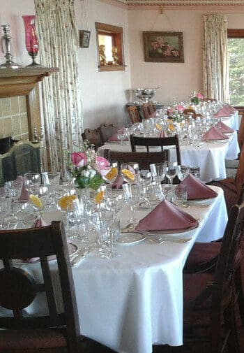 Dining room with a fireplace, with white tablecloths made up with rose trimming for Valentine's Day.