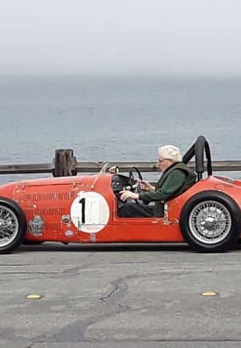 Inn owner, Don, sitting in his old, classic, red MG racing car alongside the Pacific ocean