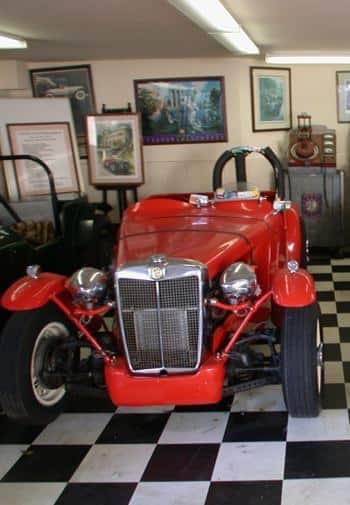 Display room with black and white checkered floors and an old classic red MG automobile