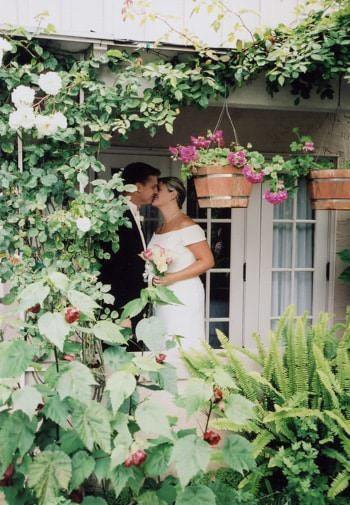 Bride in white and groom in black kissing on the porch surrounded by lush green vines and plants