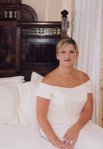 Beautiful bride with updo, off the shoulder white wedding dress, sitting on a bed and smiling