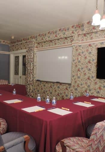 Meeting room with floral papered walls, tables lined up in an