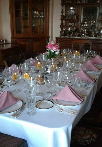 Dining table set for a meal with white cloth, pink napkins, several wine glasses and fresh pink roses