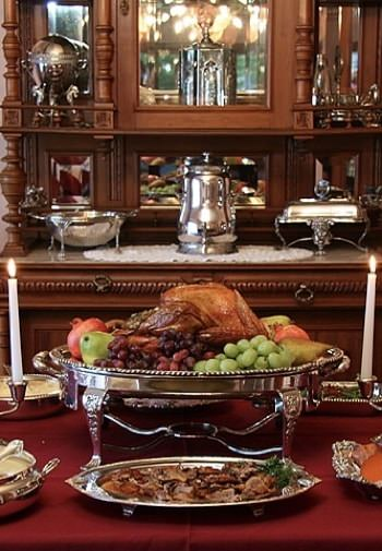 Dining table with raised silver platter topped with roasted turkey and fresh fruit, buffet topped with silver serving dishes