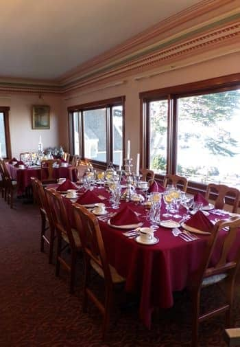 Dining room with windows overlooking the Bay, tables topped with burgundy cloths and napkins and set for a meal