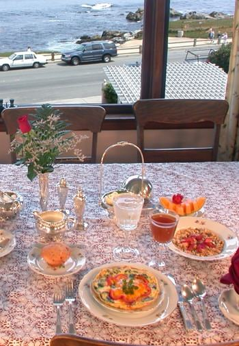 Close-up view of table with ivory lace topper, plates with baked quiche, granola and fruit, juice, and water overlooking the Bay