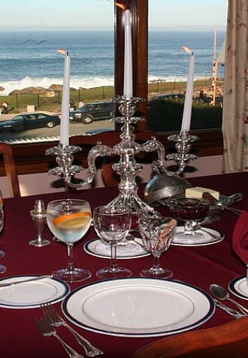 Close up view of table set with silver triple candelabra, white plates, and wine glasses overlooking Monterey Bay