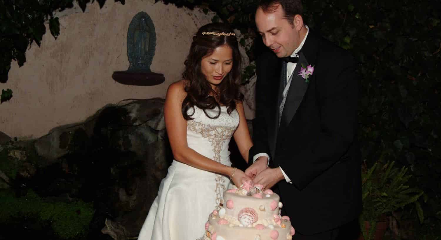 Bride and groom cutting a multi-teared pink wedding cake