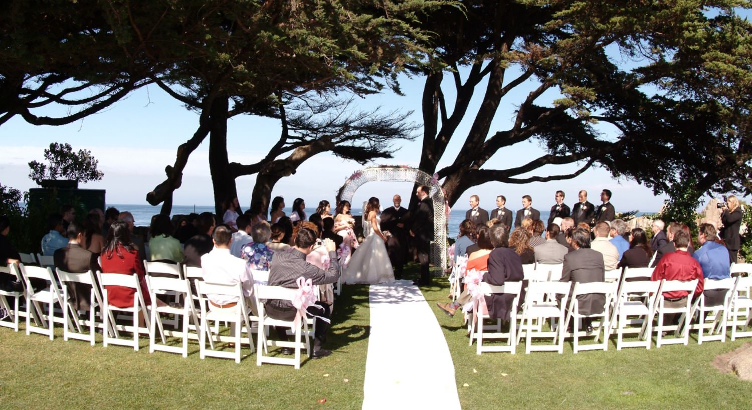 Outdoor wedding under shade tree with ocean views, white aisle runner and rows of white chairs