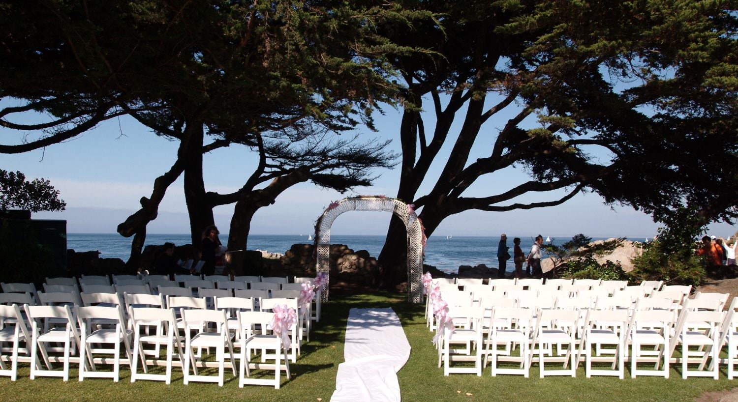 Set up before an outdoor wedding, arched trellis, aisle runner and rows of white chairs