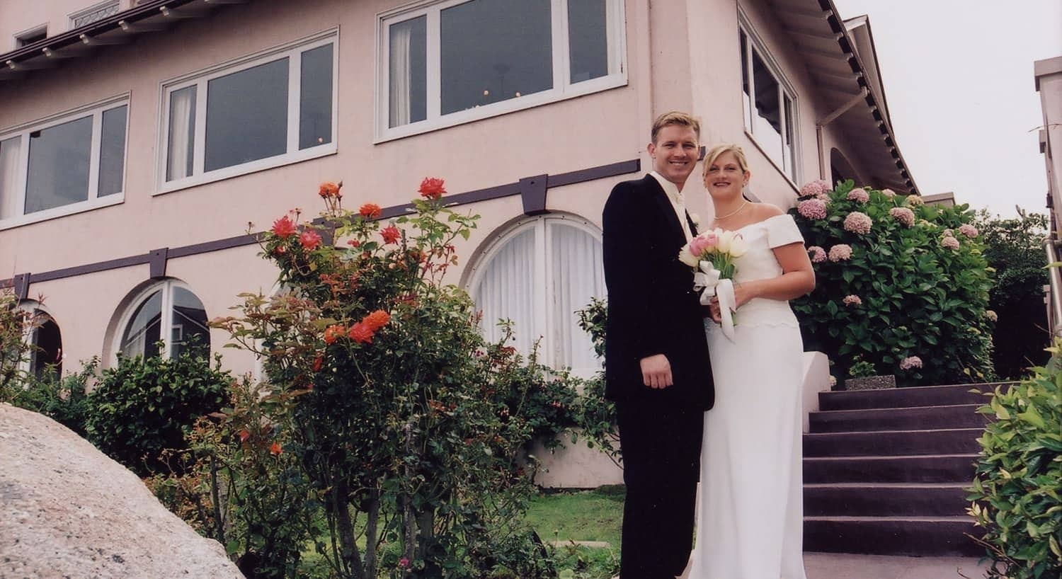 Bride and groom standing outside the pink inn surrounded by flowering plants
