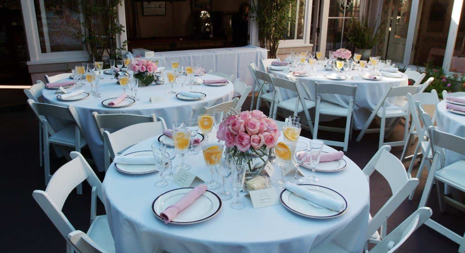 White round tables and chairs set with white plates, pink napkins and flowers for a wedding