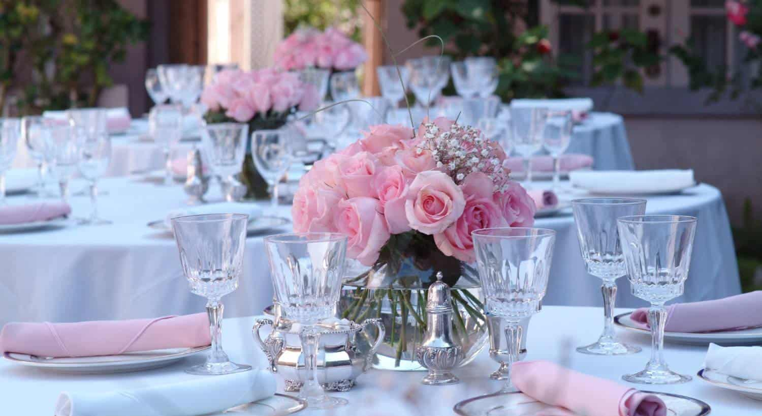 Beautiful white round tables with chairs set for a wedding with pink napkins and pink roses