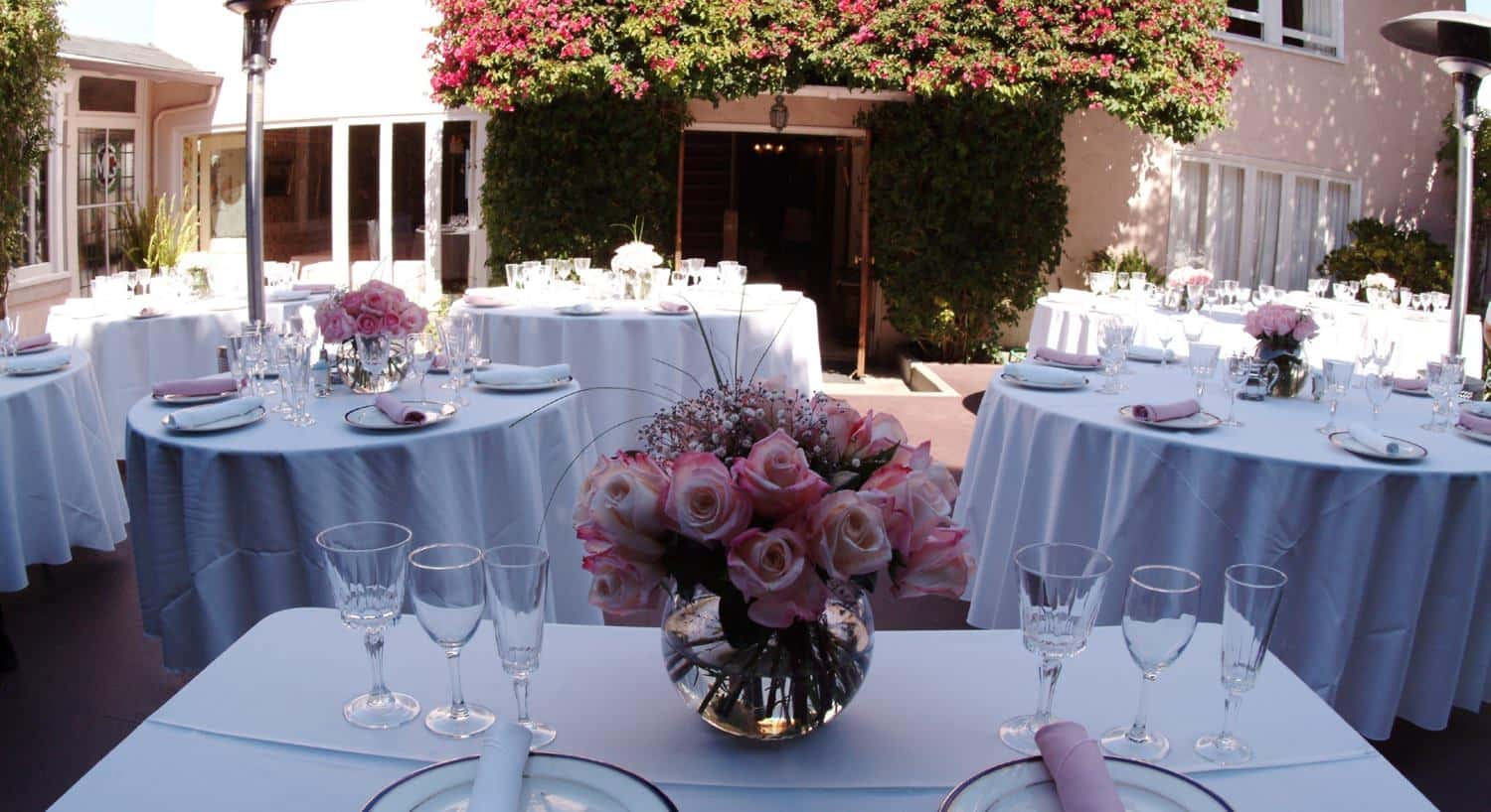 Wedding tables dressed in white with pink napkins and pink roses