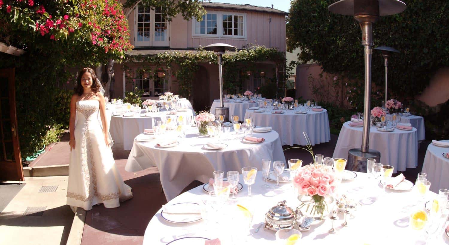 A bride standing by white round tables outside set for a wedding with pink roses
