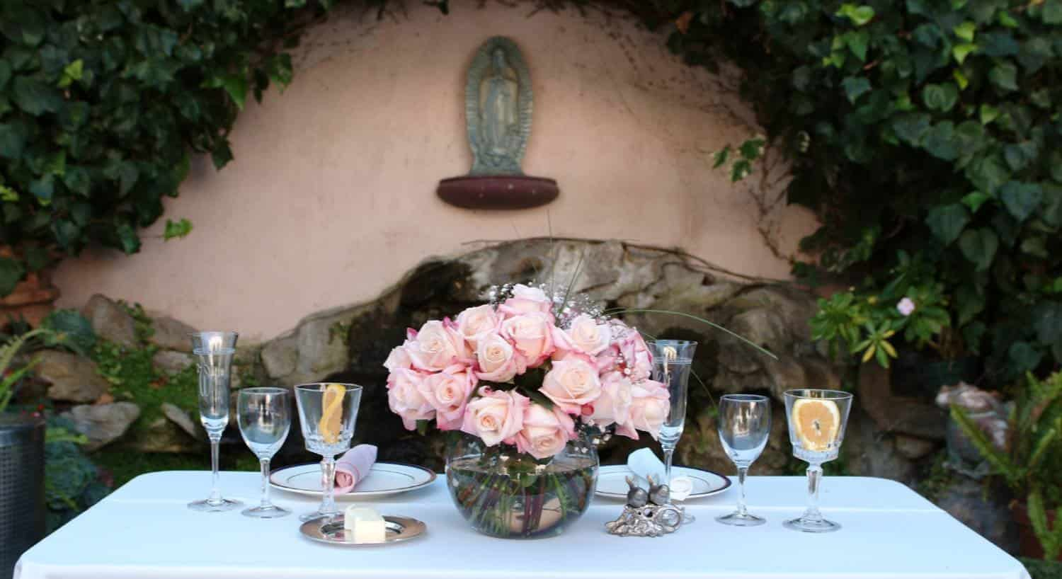 Bride and grooms white square table topped with pink roses, wine glasses, white plates and pink napkins